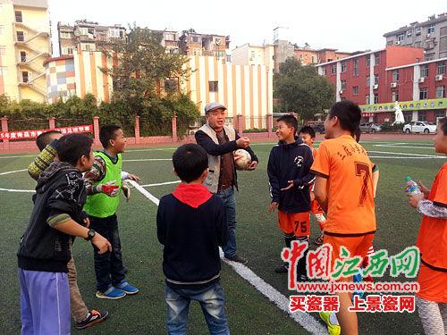 三店小学孩子们在听老师指导踢足球